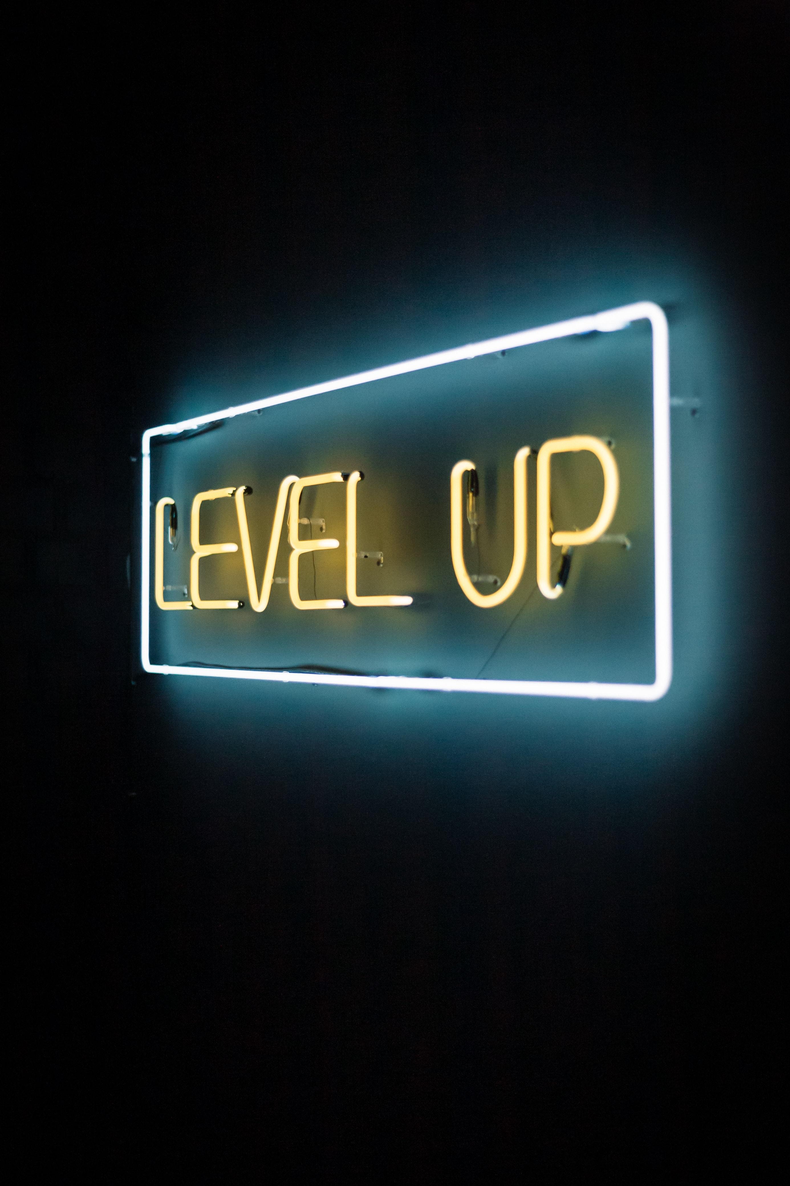"""Photo d'un écriteau artistique néon disant : """"Level Up"""""""