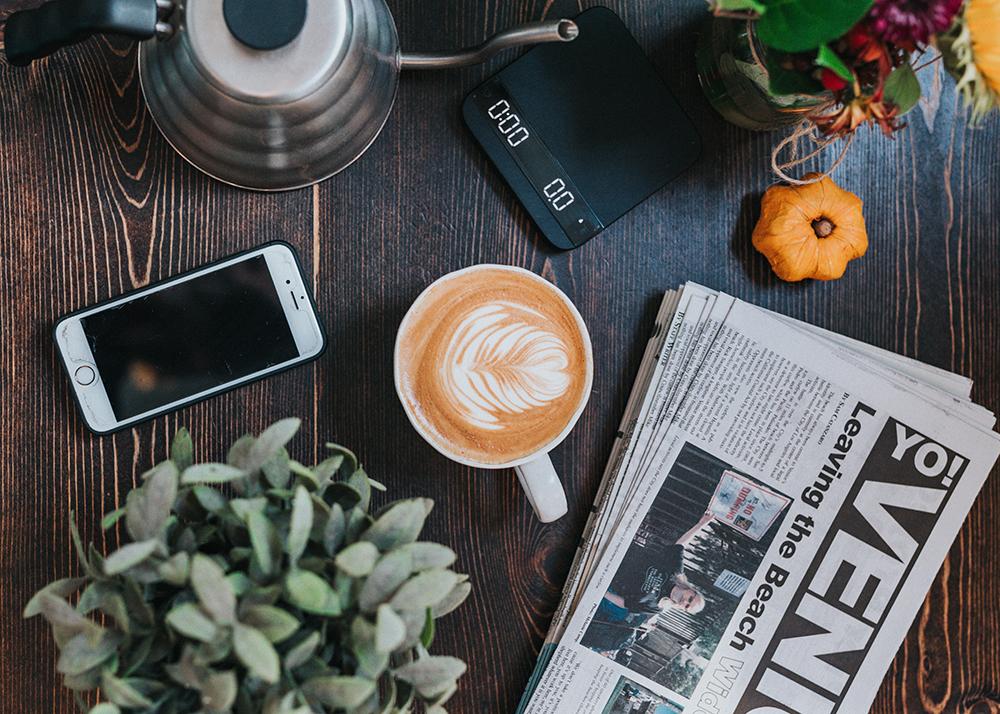 Photo d'un smartphone, d'un journal et d'un café posés sur une table.